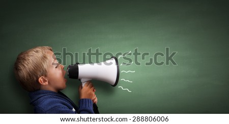 Child speaking through a megaphone against a blackboard with copy space - stock photo