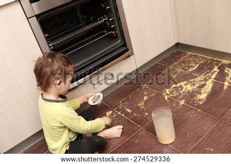 Child spilling cereal in the kitchen at home - stock photo