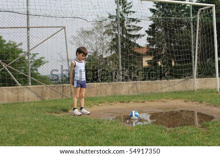 Child standing on a football court and observing a puddle - stock photo
