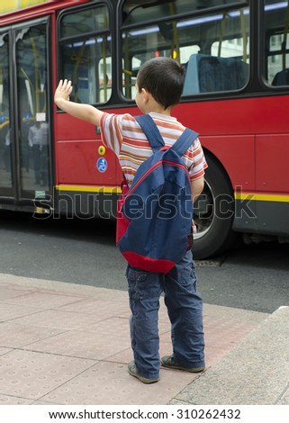 Child standing on a sidewalk or pavement waving to a red public transport bus
