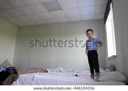 Child standing on bed in a motel - stock photo