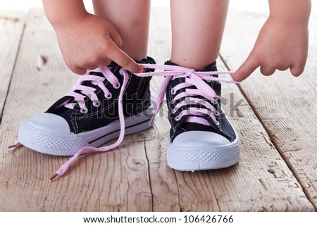 Child successfully ties shoes - closeup on feet and hands - stock photo
