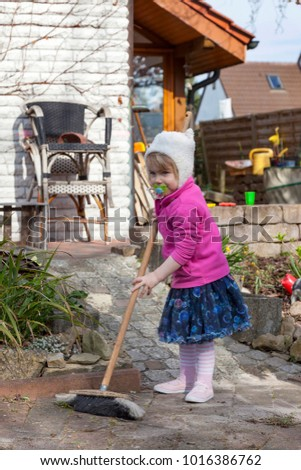 child sweeping the garden path with a broom