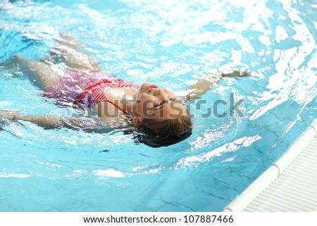 Child swimming backstroke in the pool - stock photo