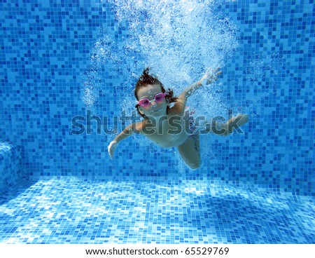 Child swimming underwater in the pool - stock photo