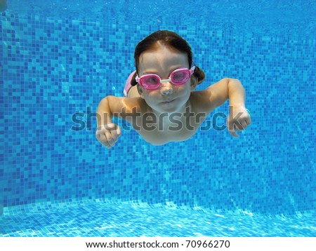 Child swimming underwater in the pool