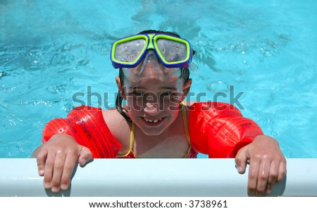 Child Swimming With Goggles and Floaties - stock photo