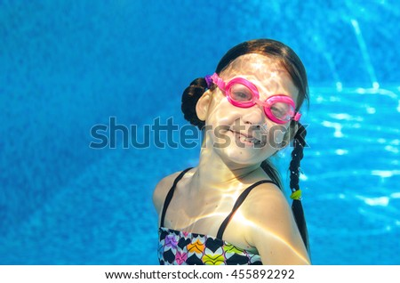 Child swims in pool under water, funny happy girl in goggles has fun and makes bubbles, kid sport on active family vacation  - stock photo
