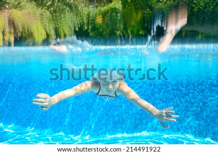 Child swims in swimming pool, playing and having fun, underwater and above view, kids sport and vacation   - stock photo