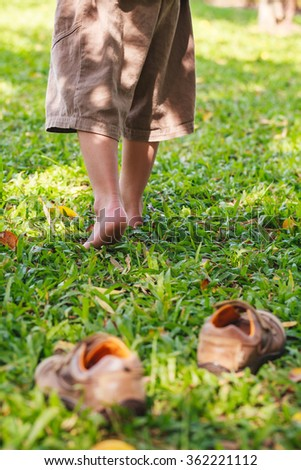 Child take off leather shoes. Close up child's foot learns to walk on grass, reflexology massage. Kid relax in garden. Shallow depth of field (dof), selective focus. - stock photo