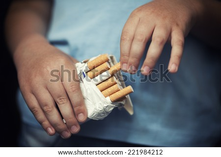 Child takes out cigarette from pack of cigarettes.