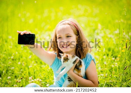 Child taking photo with mobile phone camera of herself and her cat - outdoor in nature - stock photo