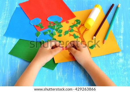 Child tears a red paper into small pieces. Child holds red paper pieces in his hands. Kindergarten art lesson. Set of color paper, pencils, glue stick on wooden background. Fun paper crafts for kids - stock photo