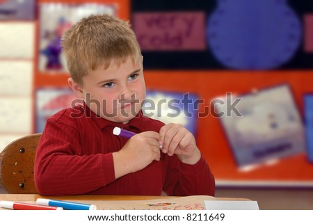 Child thinking about what to color with markers - stock photo