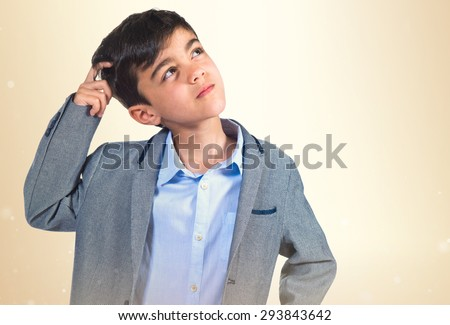 Child thinking over ocher background