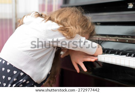 Child tired of learning the piano. - stock photo