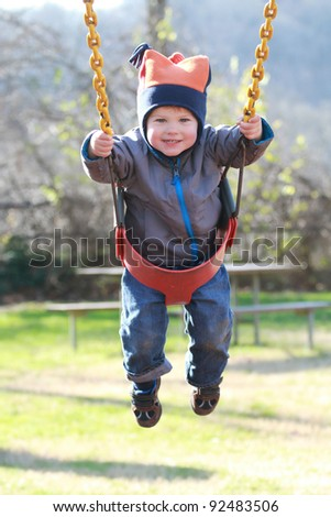 Child, toddler boy on a swing at a playground, smiling and happy