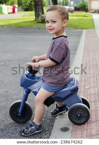 Child toddler playing riding a toy bike at a residential street with pavement. - stock photo