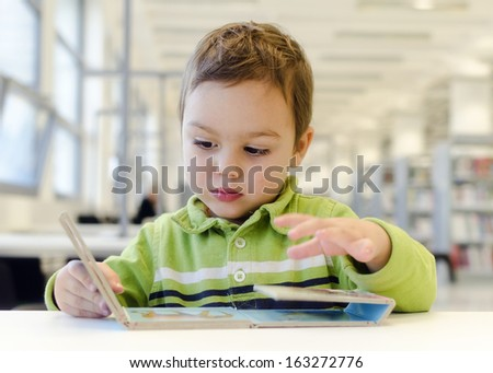 Child toddler reading children picture book on low table in public library. - stock photo