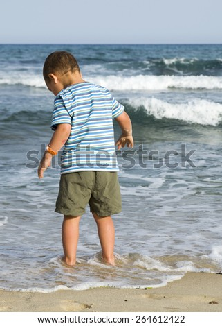 Child toddler standing at sand beach in the shallow of water in the sea, back view. - stock photo