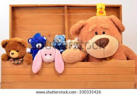 Child trunk with a big teddy bear and small plush toys. Chest with cute baby toys. - stock photo