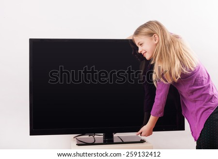Child TV addiction example -  Cute girl hugging the tv in front of a white background  - stock photo
