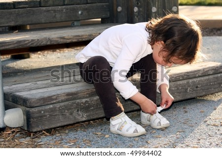 Child tying her shoe - stock photo