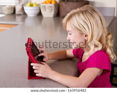 Child using a tablet computer, sitting at a table in kitchen at home