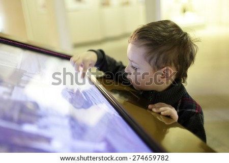 Child using touch screen in the museum - stock photo
