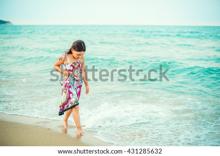 Child walking along the seacoast. Girl in a colorful dress walking on the beach - stock photo