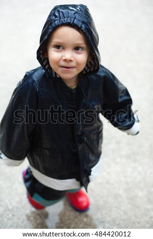 Child walking in rain with wet face and raincoat