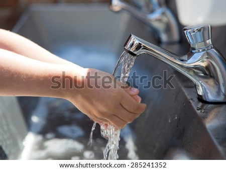 Child washing hands in a steel basin