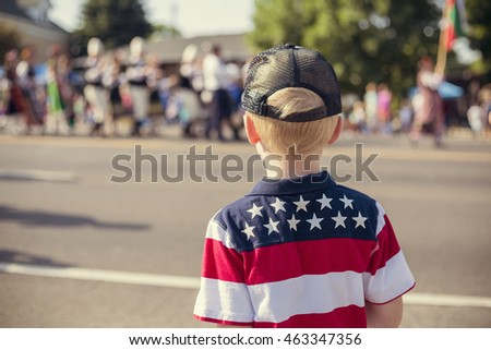 Child watching an Independence Day Parade on a summer day