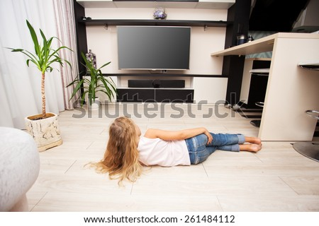 Child watching TV at home. Girl looking at television - stock photo