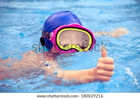 Child wearing a colorful swimming mask swimming in an open-air swimming pool - stock photo