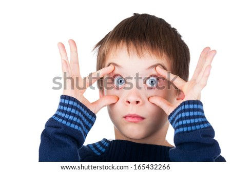 Child wearing blue sweater making funny face holding his eyes wide open on white background - stock photo