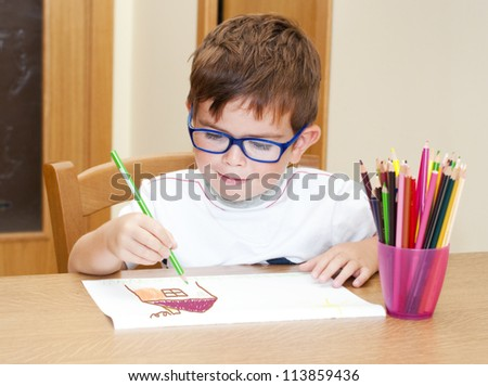 Child wearing glasses drawing a house with pencils