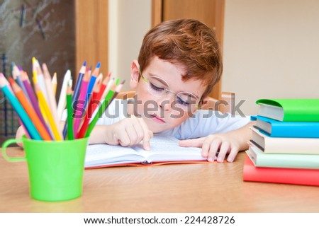 Child wearing glasses reading a book at a desk  - stock photo