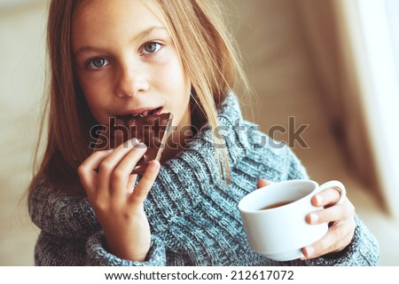 Child wearing sweater and drinking tea at home - stock photo