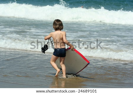 child with a bodyboard on the beach