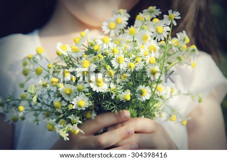 Child with a bouquet of daisies on nature - stock photo