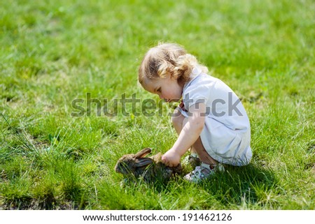 child with a rabbit on the grass - stock photo