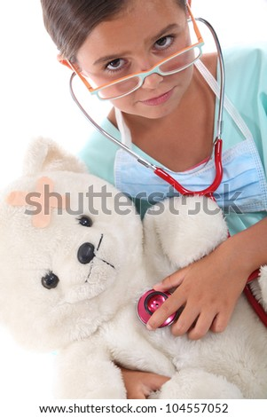 Child with a stethoscope checking the health of her teddy - stock photo