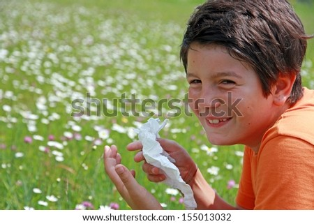child with an allergy to pollen while sneeze in the middle of the flowers - stock photo