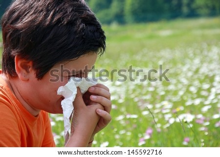 child with an allergy to pollen while you blow your nose with a white handkerchief - stock photo