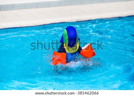 Child with armbands and sun protection clothing playing outside in the children's pool.