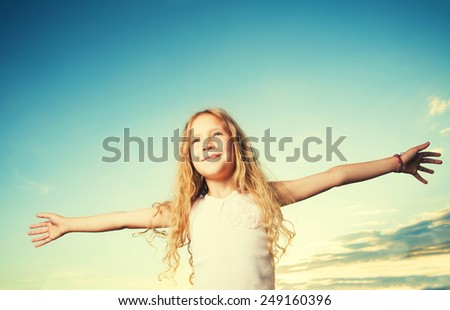 Child with arms outstretched. Freedom. Girl on a background of the sky - stock photo