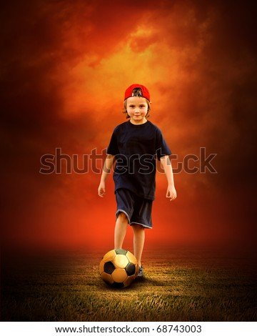 Child with ball in fires flame on the outdoors field - stock photo