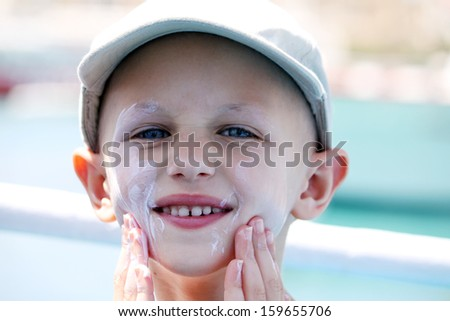 child with cancer applies sun cream on her face  - stock photo