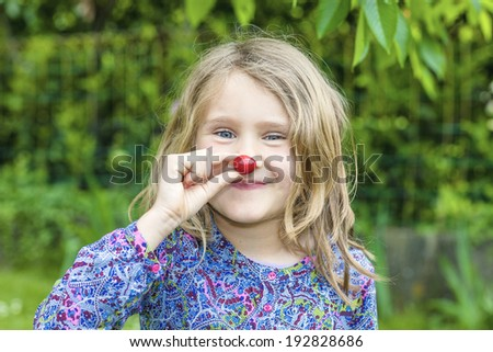 Child with cherry in the hand in a garden - stock photo
